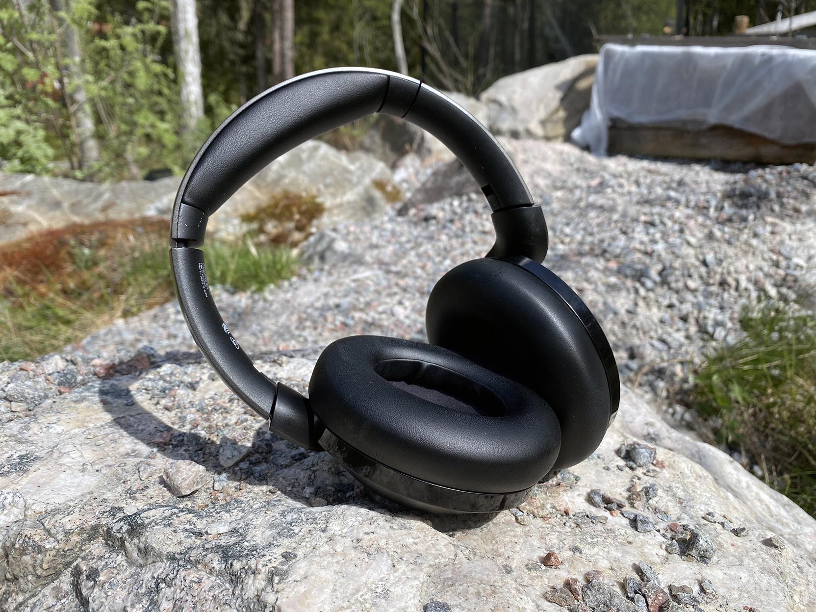 Billede af Philips TAPH805 høretelefonerne, som ligger og soler sig på en sten